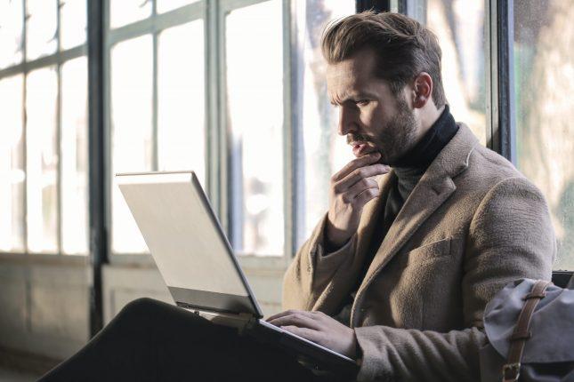 Ένας άνδρας κρατάει το πιγούνι του και κοιτάει με απορία τον υπολογιστή